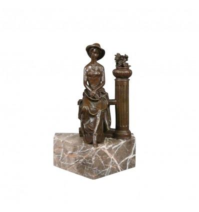 Bronzová socha ženy sedící na zábradlí -